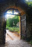 Stone arch with forged iron gates in a summer garden. View of a arched opening in a  stone wall, with opened forged iron gates, in beautiful gardens, at sunset Stock Photos