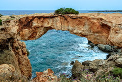 Stone arch over coastline Royalty Free Stock Images