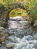 Stone arch over rushing stream Stock Image