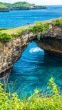 Stone arch over the sea. Broken beach. Rock coastline. Nusa Penida, Indonesia. Royalty Free Stock Photography