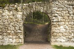 Stone arch, semi-circular roof of the passageway in an old stone wall, manhole entrance aperture the grotto. Stone arch, a semicircular arch passage in the stone royalty free stock images