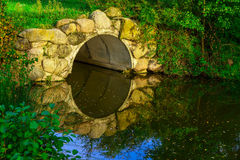 Stone Arch and Trees Reflecting in Lake Royalty Free Stock Photo