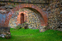 Stone arch and wall in internal courtyard. Of castle with green grass and doorway Stock Images