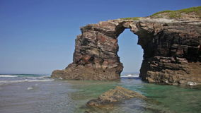Stone arches on Playa de las Catedrales during outflow stock video