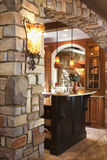 Stone Archway in Affluent Home. Stone archway framing dark wood cabinet with marble counter top in luxury home. Vertical shot Stock Photos