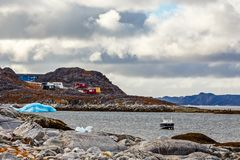 Stone arctic coast, motorboat and blue iceberg floating in the b Royalty Free Stock Photography