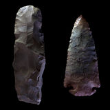 Stone Arrow Head. An arrowhead, and a stone knife, isolated on black Stock Photos
