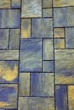 Stone background from a fragment of gray green colored paving tiles on the road Royalty Free Stock Photo