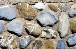 Stone background in gray, brown, orange and blue hues. Stones of various shapes, background, Tyrrhenian sea, in Livorno, Salivoli Tuscany, Italy. Beautiful stock image