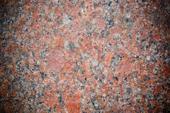 Stone Background of mottled red granite igneous rock. With darkened edges, texture Royalty Free Stock Photos