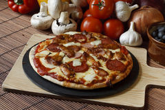 Stone baked Meat feast gourmet Pizza. Barbecue or BBQ meat feast pizza with a topping of pepperoni, sausage, salami and chicken wings Stock Images