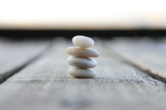Stone balance. Stones on the wooden pier Stock Image