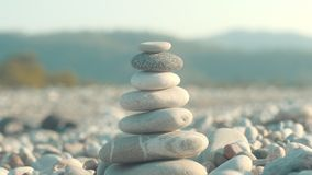 Stone balance closeup. Female hand making pebbles tower from sea stones stock video footage