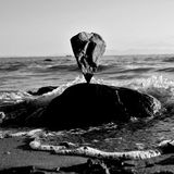 Stone balance in the ocean. One stone balanced on another with the waves behind in the ocean Stock Image