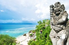 Stone balinese statue Blue sea sky tropical sand beach stock photography