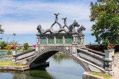 Stone balinese style arch bridge. In a park with gragon images, Tirtaganga, Bali Stock Photos