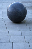 Stone ball. Architectural detail: large stone ball on a pavement Royalty Free Stock Images