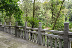 Stone balustrade of flagstone paved platform in woods Stock Photography