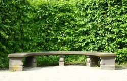 Stone Bank. Semi-circular stone bench in front of a green hedge royalty free stock photo
