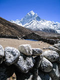 Stone barn with snow mountains in himalayas Royalty Free Stock Photo