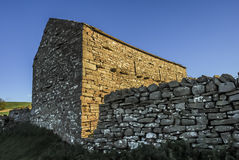 Stone Barn. And wall with early morning sunlight Stock Photo