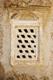Stone barred window in stone wall. A view of a window with heavy  bars in an old stone wall Royalty Free Stock Images