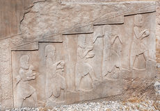 Stone bas-relief with images of people bringing food and animals, as donations, in historical Persepolis, Iran. Royalty Free Stock Photo