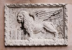 Stone bas-relief of the Venetian lion on one of the houses of Venice. The lion of St. Mark is a symbol of the city of stock image