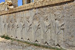 Ruined bas-relief with guards carved on wall of sandstone, Iran. Royalty Free Stock Photos