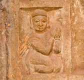 Stone bas-relief with woman clasped her hands together in prayer Stock Images