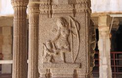 Stone bas-reliefs on the column in Shiva Virupaksha Temple, Hampi. Carving stone ancient background. Carved figures made of stone. Unesco World Heritage Site stock images