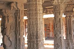 Stone bas-reliefs on the column in Shiva Virupaksha Temple, Hampi. Carving stone ancient background. Carved figures made of stone. Unesco World Heritage Site stock photography