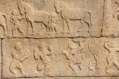 Stone bas-reliefs on the walls in Temples Hampi. Carving stone a. Ncient background. Carved figures made of stone. Unesco World Heritage Site. Karnataka, India royalty free stock photos