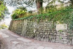 Stone based slope with wooden fance on it and the old road Royalty Free Stock Photo