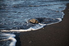 Stone bathed by waves on a beach in California. A wave reaches a stone on the US west coast Royalty Free Stock Image