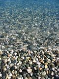 Stone beach. Round pebbles with blueturqiose water floating ontop. water crashing 3/4 of the way down the photo. clear unsubmerged pebbles on bottom third of Royalty Free Stock Images