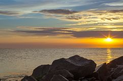 stone beach on the background of the sea, sunset in the clouds. stock photos