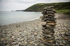 A pyramid of stones on the shore of the sea of Japan. Stone beach and a cairn. Japanese Sea. Island Russian stock photography