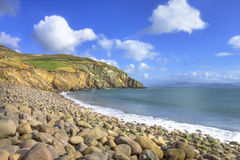 A stone beach with cliffs in background, Ireland. Stock Image