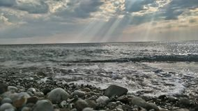 Stone beach. With cloud and sunny rays Stock Image