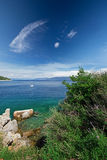 Stone beach with crystal clear tourquise sea with pine tree in Croatia, Istria, Europe Royalty Free Stock Photos