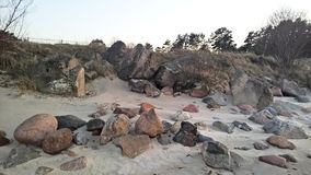 Stone beach. Dunes, evening. Colored stones in the sand Stock Images