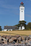 Stone beach and lighthouse Royalty Free Stock Photos