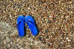 Stone beach with pair of blue slippers and waves move. Closeup. Stone beach with pair of blue slippers and waves move them. Closeup stock images