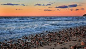 Stone beach. In the rays of the setting sun Royalty Free Stock Photos