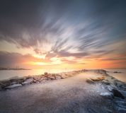 Stone beach shore Barcelona at dramatic sunrise Royalty Free Stock Photo