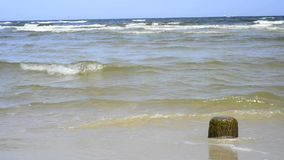 Stone at a beach with soft break-wave at the Baltic sea Royalty Free Stock Image
