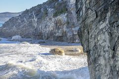 Stone beach surrounded by cliffs with oncoming foamy waves. Greece royalty free stock image