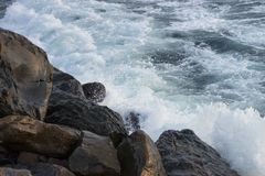 Waves crash on the rocks. Stone beach. A troubled sea. Foamy waves. Alarm. The sound of the sea. Storm on the shore Royalty Free Stock Image