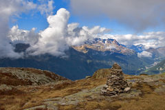 Stone beacon. A panorama of Mont Blanc in easy clouds, a high-mountainous meadow and a pyramid stones showing road stock photos